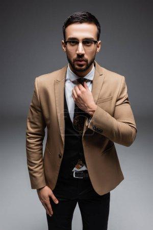 Photo pour Jeune homme arabe en costume élégant, ajuster la cravate tout en regardant la caméra sur gris - image libre de droit