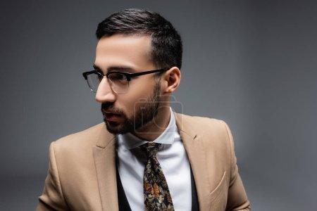 Photo pour Brunette musulman dans les lunettes regardant loin sur gris - image libre de droit