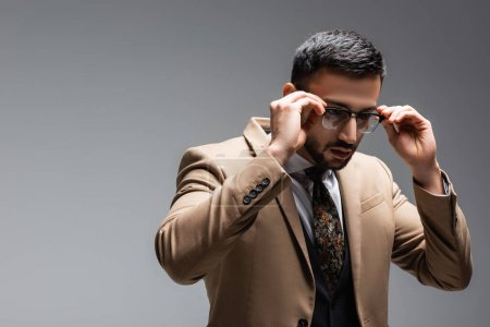 Photo for Young muslim man in beige blazer adjusting eyeglasses isolated on grey - Royalty Free Image