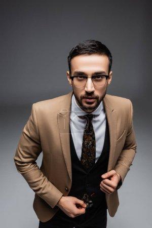 Photo pour Vue grand angle de l'homme musulman à la mode en lunettes regardant la caméra sur gris - image libre de droit