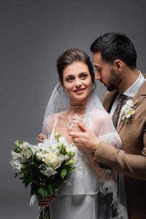 Photo pour Femme heureuse avec bouquet de mariage près fiancé musulman isolé sur gris - image libre de droit