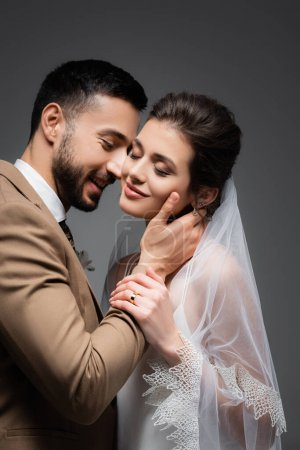 Photo for Happy arabian man hugging neck of pretty, smiling bride isolated on grey - Royalty Free Image