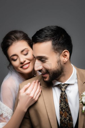 Photo for Happy bride with closed eyes hugging happy muslim groom isolated on grey - Royalty Free Image