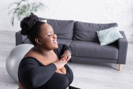 sonriente afroamericano más mujer de tamaño en ropa deportiva ejercicio en la sala de estar