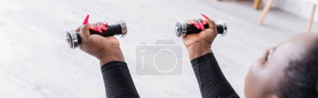 Photo for Blurred african american plus size woman in sportswear exercising with dumbbells in living room, banner - Royalty Free Image