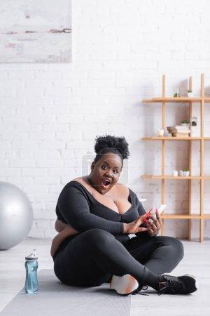 Photo pour Choqué afro-américain plus taille femme en vêtements de sport à l'aide d'un smartphone et assis sur tapis de fitness - image libre de droit