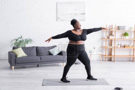 Photo pour Pleine longueur de femme africaine américaine heureuse en surpoids dans l'exercice de vêtements de sport à la maison - image libre de droit
