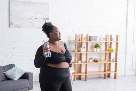 alegre afroamericana mujer con sobrepeso en ropa deportiva celebración botella de deportes en casa