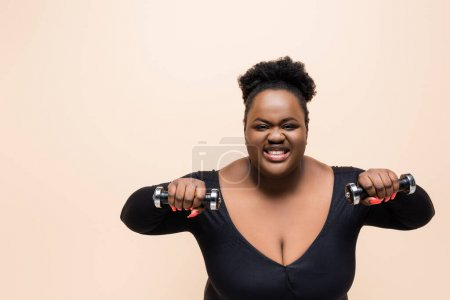 happy african american plus size woman in sportswear holding dumbbells isolated on beige