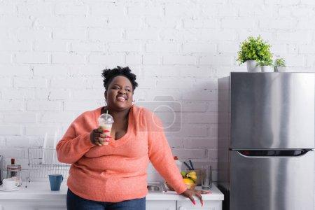 Photo pour Heureux afro-américain plus taille femme tenant tasse en plastique avec smoothie savoureux dans la cuisine - image libre de droit