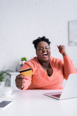 Photo for Happy african american plus size woman holding credit card near laptop - Royalty Free Image