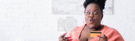 shocked african american plus size woman holding credit card and smartphone, banner