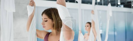 sportive woman warming up with fly yoga hammock on blurred background, banner