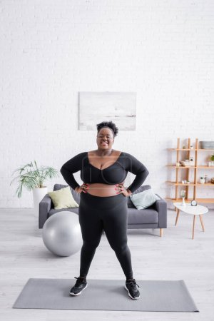 full length of african american plus size woman in sportswear standing with hands on hips on fitness mat
