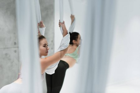 selective focus of young woman exercising with aerial yoga hammock