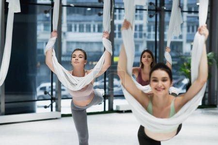 grupo de jóvenes deportistas estirándose con correas mientras practican yoga aéreo, borrosa en primer plano
