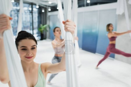 Photo for Happy young woman stretching arms with aerial yoga hammock on blurred background - Royalty Free Image