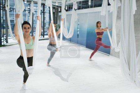 jeunes femmes sportives échauffement avec des hamacs de yoga de mouche dans la salle de gym