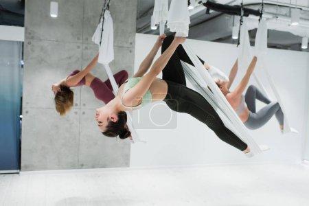 junge sportliche Frauen praktizieren Aerial Yoga im Sportzentrum, verschwommener Hintergrund