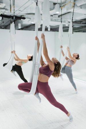 Photo pour Jeunes femmes sportives s'étirant sur des hamacs de yoga aérien dans le centre de fitness - image libre de droit