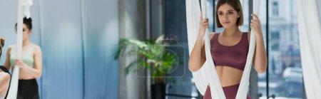 Photo pour Sportif positif échauffement avec hamac de yoga aérien sur fond flou, bannière - image libre de droit