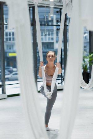 junge Sportlerin streckt Bein mit Fliegengurt auf verschwommenem Vordergrund