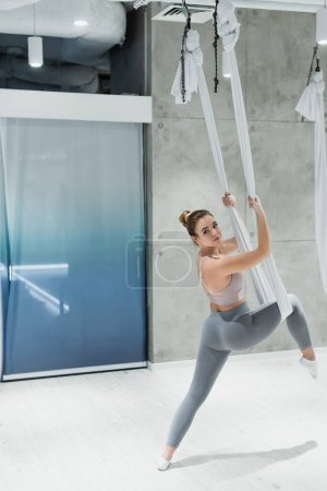 young sportswoman stretching with fly yoga hammock in gym