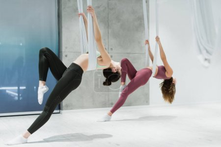 young sportive women exercising with fly yoga hammocks in sports center