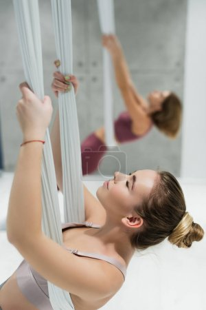 young woman with closed eyes training with aerial yoga strap in sports center