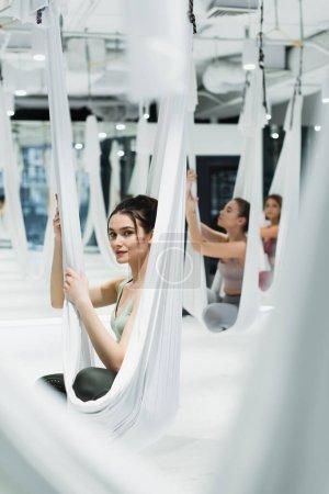 Photo pour Jeune femme regardant la caméra tout en pratiquant le yoga de mouche près du groupe sur fond flou - image libre de droit
