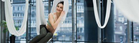 smiling woman looking away while relaxing in aerial yoga hammock, banner