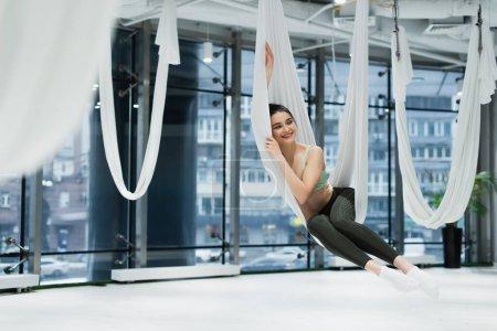 mujer alegre que mira lejos mientras que se relaja en la hamaca del yoga de la mosca, primer plano borroso