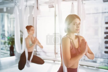 young woman looking at camera while practicing lotus pose in aerial yoga hammock, blurred background
