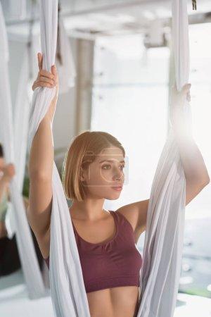 Foto de Mujer deportiva mirando hacia otro lado mientras practica yoga con mosca con hamaca - Imagen libre de derechos