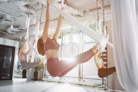 Photo for Group of sportive women practicing aerial yoga in sports center - Royalty Free Image