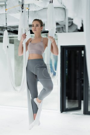 Young woman exercising with fly yoga straps in sports center
