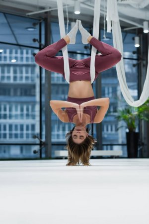 Surface level of young woman practicing aero yoga in sports center