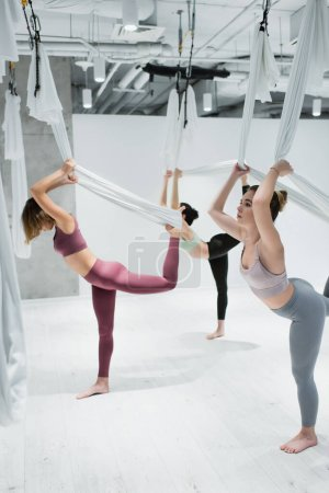 Young women exercising in group with hammocks during fly yoga