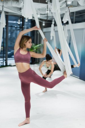 Barefoot woman exercising with hanging fly yoga hammock in fitness center