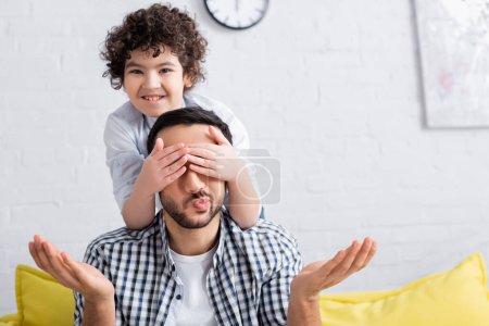 Photo pour Joyeux arabian garçon couvrant les yeux de père tout en jouant devinez qui jeu - image libre de droit