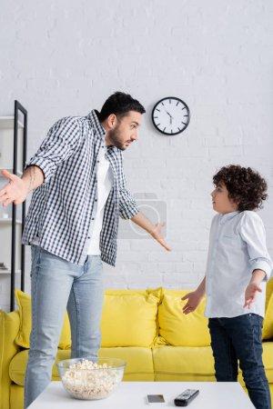 Photo pour Père arabe confus et fils montrant geste haussant les épaules tout en se regardant - image libre de droit