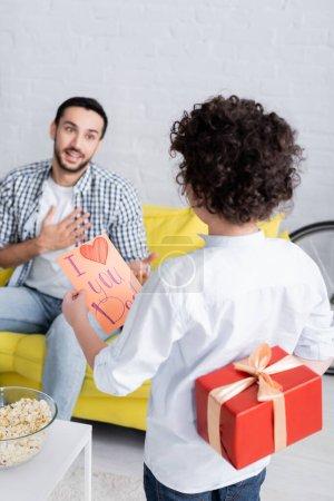 Photo pour Vue arrière de garçon avec cadeau et je t'aime carte de papa près de père étonné sur fond flou - image libre de droit