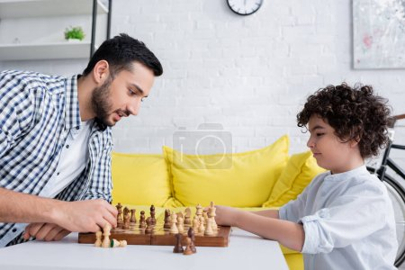 Photo for Side view of arabian father and son playing chess at home - Royalty Free Image
