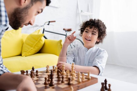 Photo for Cheerful mulsim boy pointing with finger while playing chess with father on blurred foreground - Royalty Free Image