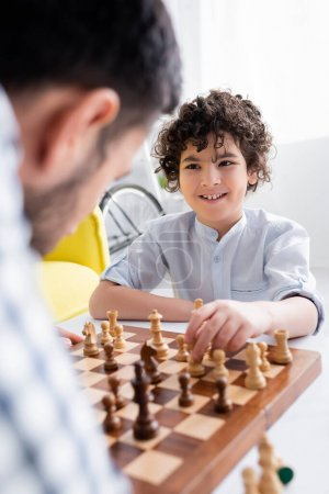 Photo for Smiling arabian boy playing chess with dad on blurred foreground - Royalty Free Image