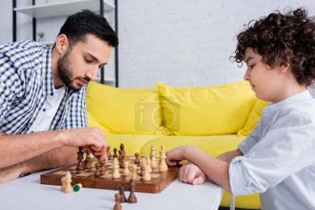 Photo for Arabian man playing chess with son at home - Royalty Free Image