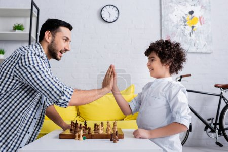 Photo for Cheerful muslim father and son giving high five near chess on board - Royalty Free Image