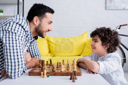 Photo for Side view of muslim man smiling at son near chess on board - Royalty Free Image