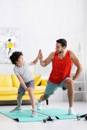 Photo pour Père musulman positif donnant haute cinq fils tout en travaillant sur des tapis de fitness à la maison - image libre de droit