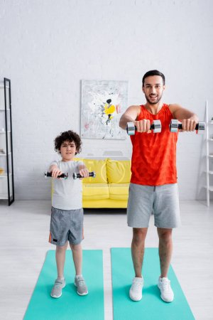 Photo for Arabian man training with dumbbells near son on fitness mat - Royalty Free Image
